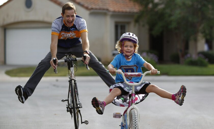 Six-year-old Hannah Higgins, who had Wilms' tumor, a type of cancer that starts in the kidneys, rides her bicycle with her father Josh Higgins while in front of their home in Escondido on Wednesday. Hannah and her father will participate in the Pedal The Cause cancer research fundraiser in San Diego this weekend. After surgery, chemotherapy, and radiation therapy, Hannah has been cancer free for the past year.