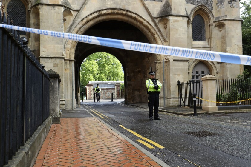 Police stand guard at the Abbey gateway of Forbury Gardens park in Reading town centre following Saturday's stabbing attack in the gardens, Sunday June 21, 2020. Thames Valley Police said a 25-year-old man from the town has been arrested and they are not looking for anyone else. (Jonathan Brady/PA via AP)