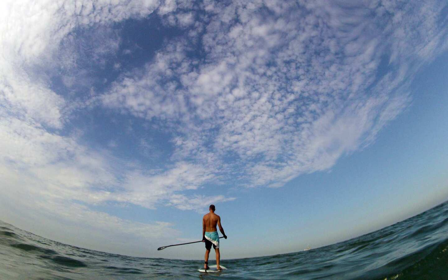 Stand-up paddle surfer Kyle Wagstaff of Park City, Utah, waits for a wave amid warm temperatures and partly cloudy skies in Huntington Beach.