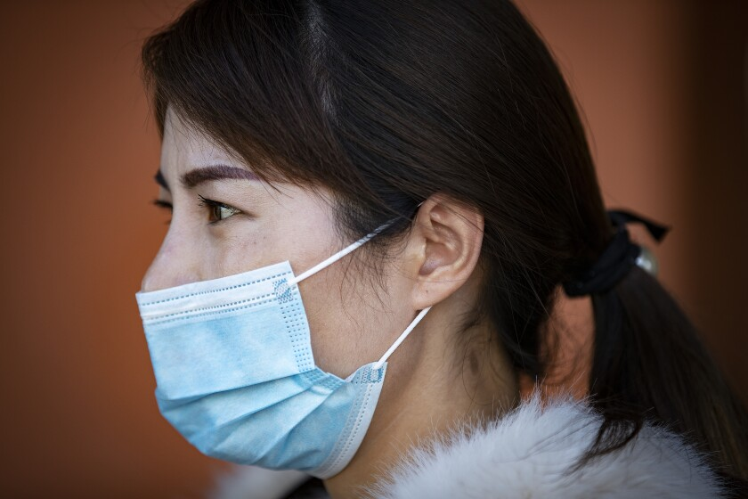 Emily Wuxue of Monterey Park wears a mask amid coronavirus fears while shopping at Ranch Market in San Gabriel.
