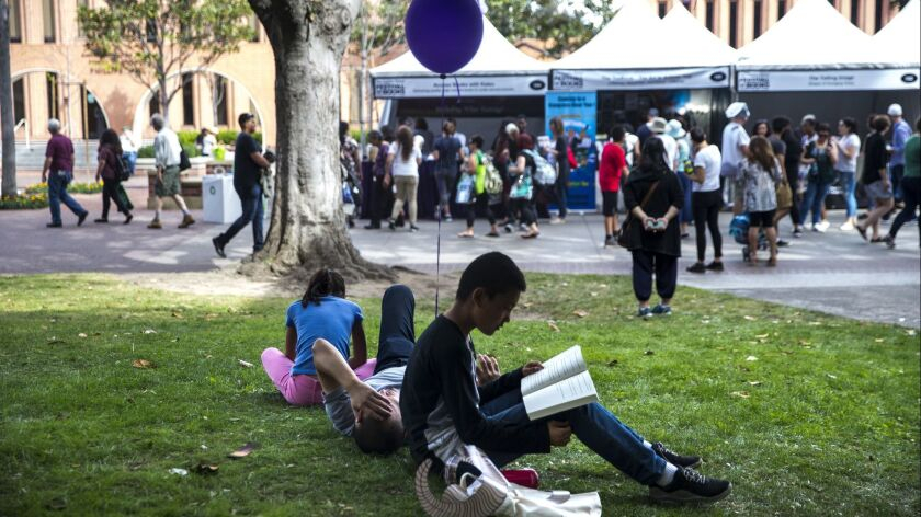 LOS ANGELES, CALIF. - APRIL 21: Adix Hu, 12, and his sister, Amy Hu, 9, read books on a grassy knoll