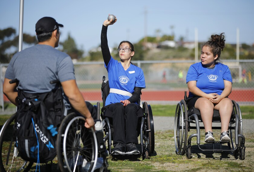 Scripps Ranch High student Ruby Melchior works on her shot put technique during an adaptive sports clinic put on by the Challenged Athletes Foundation at Clairemont High on Jan. 12, 2020. Melchior, a former pole vaulter, suffered a brain injury and is now training in the seated shot put. Coach Justin Phongsavanh, left, and Michelle Bautista look on.