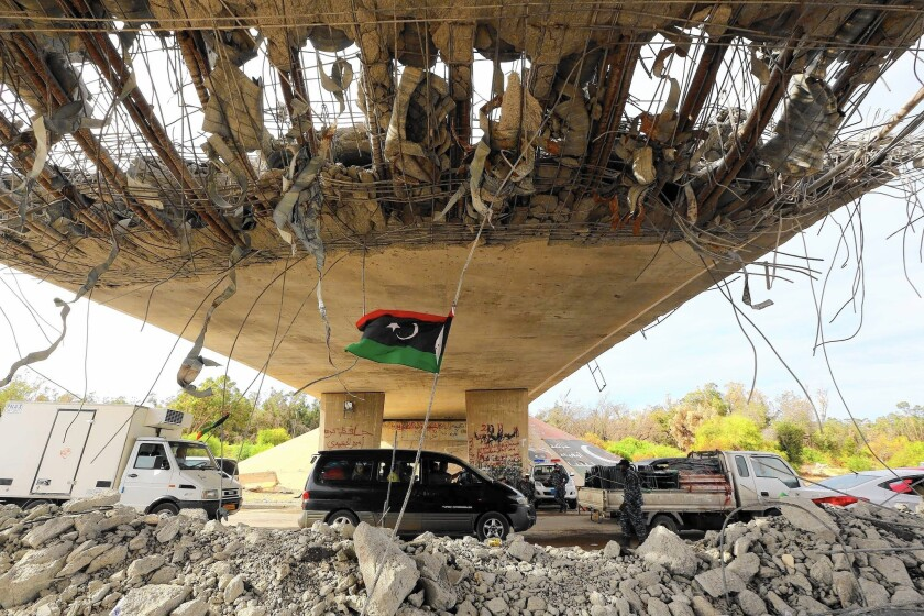 A Libyan flag flutters as cars wait at a police checkpoint near Tripoli, the capital. Neighborhoods in Tripoli and Benghazi have been smashed by battlefield-grade weapons. Most diplomats, aid groups and foreign enterprises have fled.