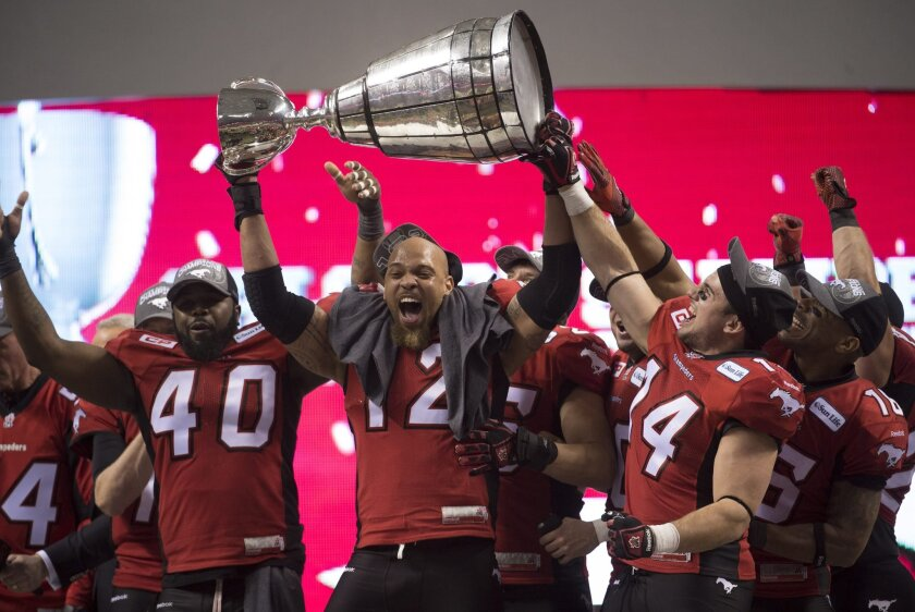 Members of the Calgary Stampeders hoist the Grey Cup as they celebrate after defeating the Hamilton Tiger-Cats in the 102nd Grey Cup CFL football game in Vancouver, British Columbia, Sunday, Nov. 30, 2014. (AP Photo/The Canadian Press, Paul Chiasson)