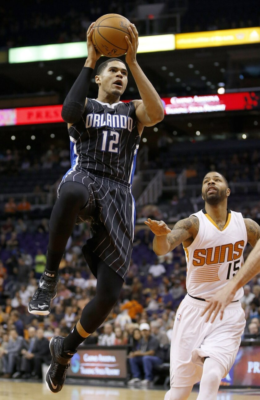 Orlando Magic's Tobias Harris (12) drives past Phoenix Suns' Marcus Morris (15) to score during the first half of an NBA basketball game Sunday, Nov. 30, 2014, in Phoenix. (AP Photo/Ross D. Franklin)