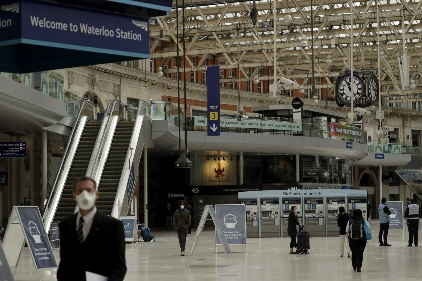 Signs recommending people wear face coverings to help stop the spread of coronavirus are displayed in Waterloo station, London, Thursday, June 4, 2020. Waterloo station, which is wide recognised as the busiest train station in Britain, is still much quieter than normal as most commuters are working from home and not commuting into central London offices. (AP Photo/Matt Dunham)
