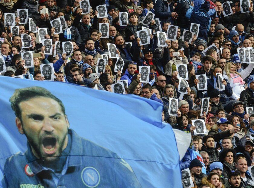 A giant flag with Napoli player Gonzalo Higuain is seen as Napoli supporters hold up prints of Napoli defender Kalidou Koulibaly's portrait in his support ahead of a Serie A soccer match between Napoli and Carpi, at the San Paolo stadium in Naples, Italy, Sunday, Feb. 7, 2016. Last week during the
