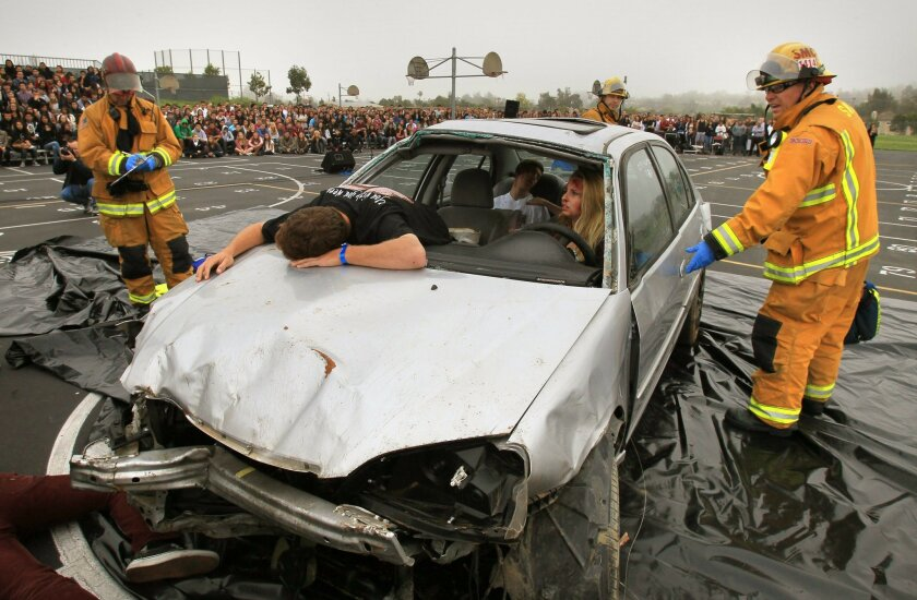 """An emergency official checks an accident """"victim"""" as students stage a re-enactment of a DUI crash at Mission Hills High School."""