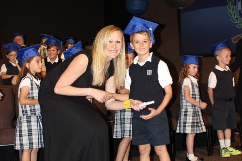 Horizon Prep kindergarten graduate P.J. Rogers receives his diploma from teacher Krista Roark.