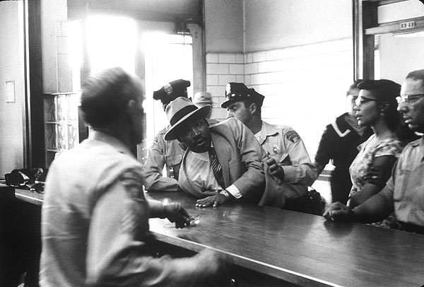 Montgomery, Ala., 1958: The Rev. Martin Luther King Jr. is sprawled across the booking desk at a police station as his stunned wife, Coretta, looks on. He was arrested for loitering at the Montgomery Courthouse and released when his identity became known to the police.