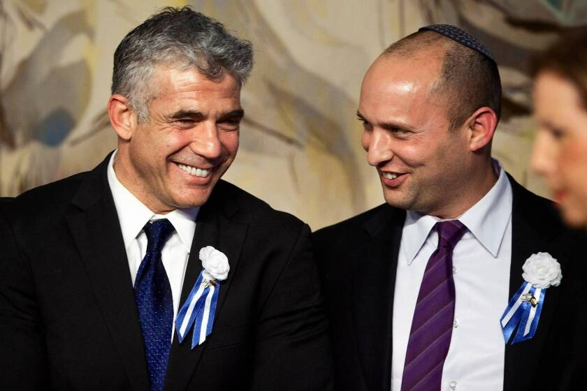 Rivals Yair Lapid, left, leader of the Yesh Atid party, and Naftali Bennett, head of the Jewish Home party, attend a reception this month in Jerusalem. Both support a military draft for the ultra-Orthodox.