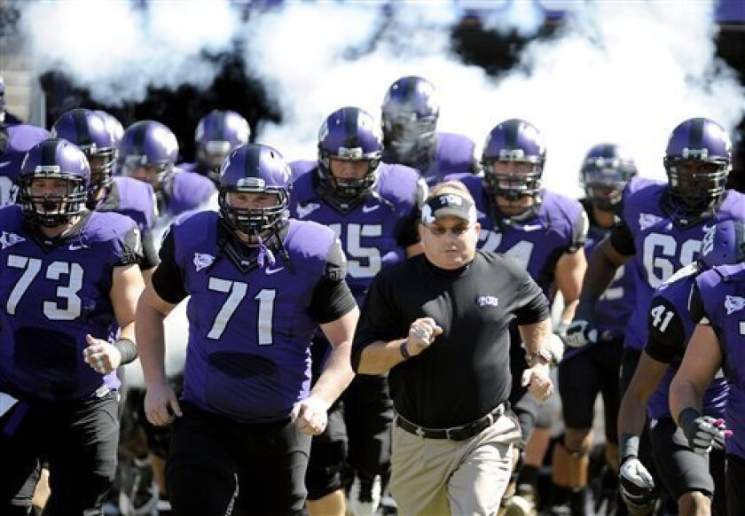 TCU head coach Gary Patterson runs onto the field with his team on Oct. 1.