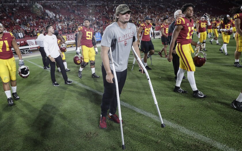USC quarterback JT Daniels is on crutches as he makes his way onto the field.