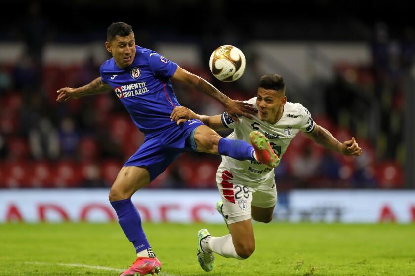 Julio Domínguez, del Cruz Azul, disputa un balón con Mario Quiroga, del Pachuca, en un partido de la Liga MX, el sábado 22 de mayo de 2021 (AP Foto/Fernando Llano)