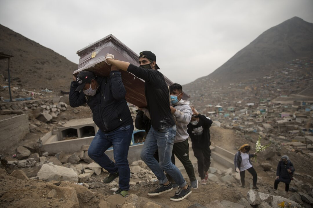 Relatives of Ronald Palomo, carry his coffin for burial at the cemetery in Comas on the outskirts of Lima.