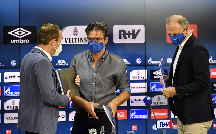 Marketing board Alexander Jobst, head coach David Wagner and sports director Jochen Schneider, from left, gather together after a press conference of Bundesliga club FC Schalke 04 at the arena in Gelsenkirchen, Germany, Wednesday, July 1, 2020. The traditional soccer club went into trouble following fan unrest because of the club's lengthy winless run, financial troubles and the resign of Schalke chairman Clemens Toennies. The controversial Schalke boss faced an outbreak of coronavirus at a slaughterhouse owned by his company and was made responsible by the public for the following lockdown in the Guetersloh district. (AP Photo/Martin Meissner)