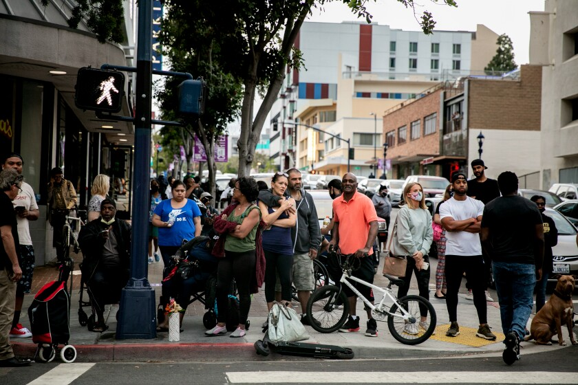 A crowd gathers on Sixth Avenue in Downtown San Diego where San Diego Police Department officers shot a man.
