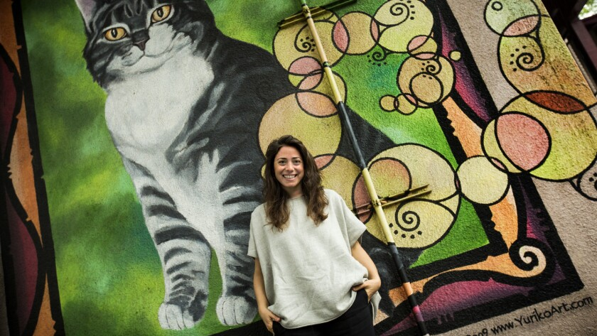Director Ceyda Torun stands in front of a cat mural by Yuriko Art at Elysian Heights Elementary School in Los Angeles.