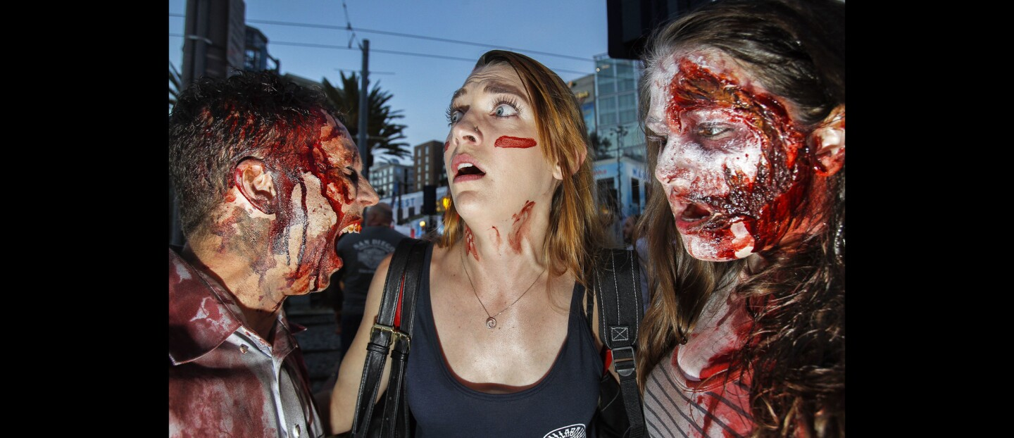 Lauren Gilbert, center, plays the victim of zombies Brandon Keller and Sarah Poteet on 5th Avenue.
