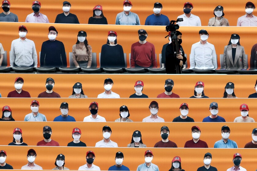A TV cameraman walks through the spectators' seating area, which is covered with pictures of fans, before the start of a baseball game between the Hanwha Eagles and SK Wyverns in South Korea.