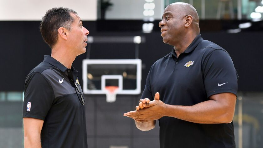 Lakers general manager Rob Pelinka, left, and Magic Johnson, president of basketball operations, chat before addressing the media on Thursday at their training facility in El Segundo.