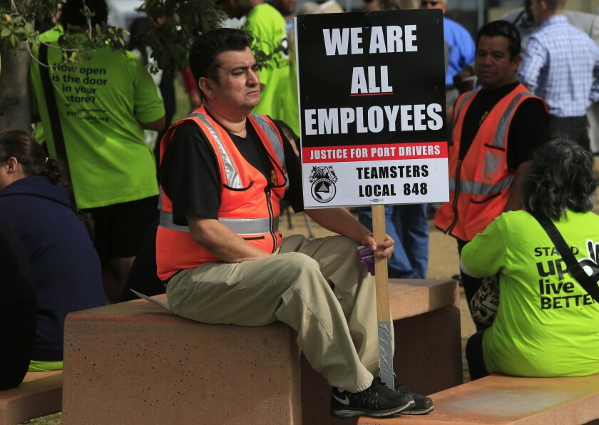 Truck drivers march with signs during a strike against short-haul trucking companies serving the ports of Los Angeles and Long Beach in November.