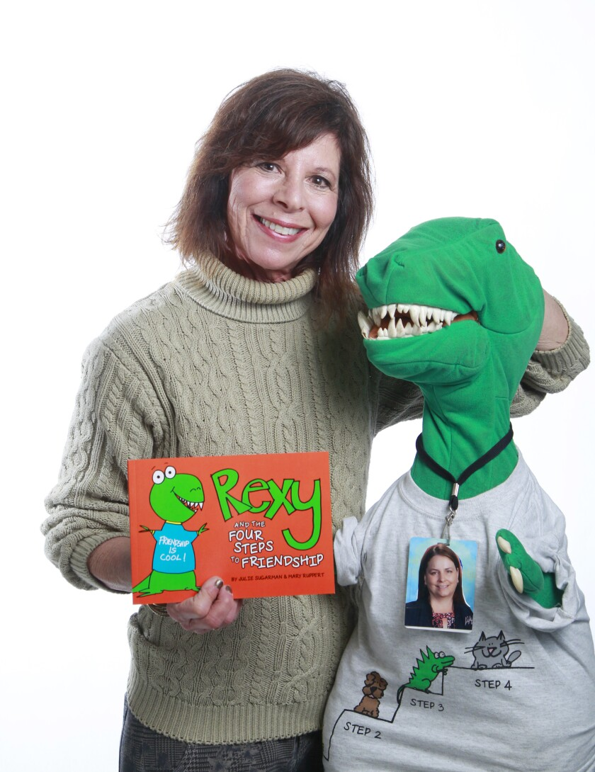 "Julie Sugarman is a kindergarten teacher who wrote a children's book with her colleague, Mary Ruppert (photograph around the dinosaur's neck), called ""The Four Steps to Friendship."" She is holding a dinosaur named Rexy, the main character of their book."