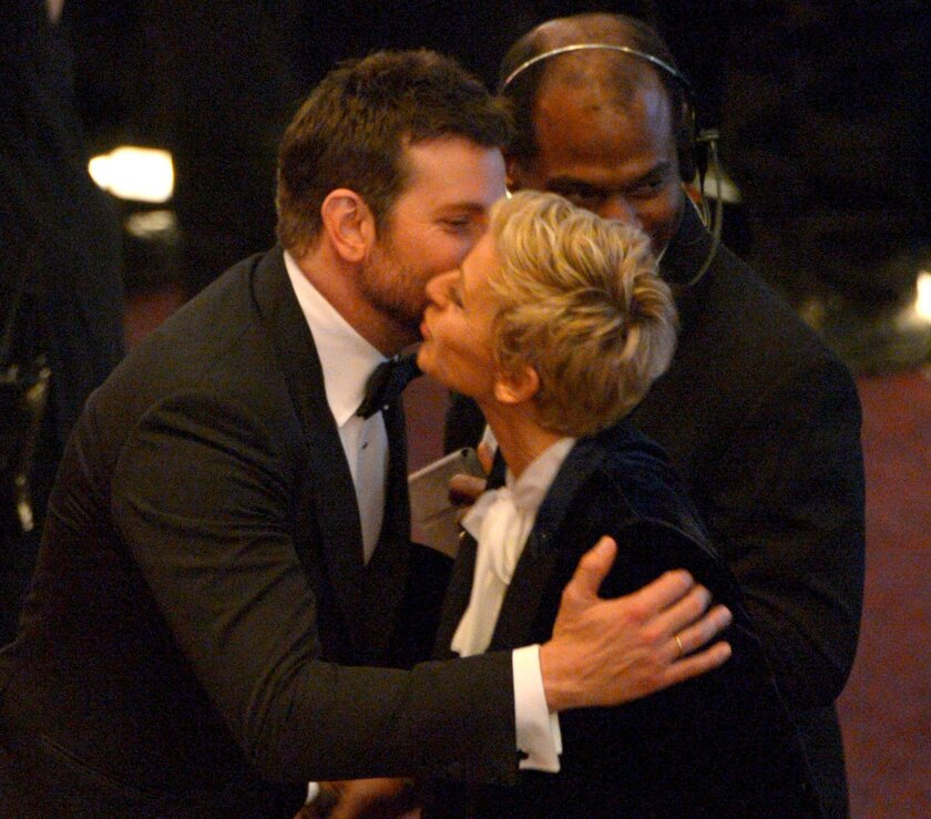 Bradley Cooper, left, and Ellen DeGeneres kiss in the audience during the Oscars at the Dolby Theatre on Sunday, March 2, 2014, in Los Angeles.  (Photo by John Shearer/Invision/AP)