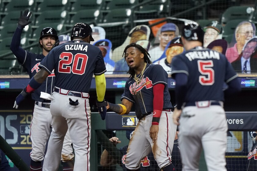 Atlanta Braves' Ronald Acuna Jr. and Dansby Swanson congratulate teammates.