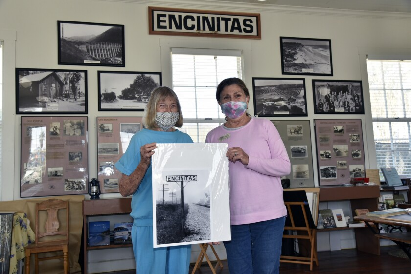 Pam Hammond Walker (great great grandaughter of schoolhouse builder EG Hammond) and Encinitas Historical Society Vice President Dana Donatelli hold a photo of a railroad sign that was recently added to the Society's collection