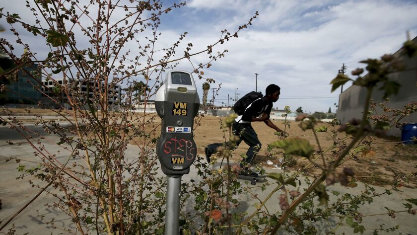 LOS ANGELES, CALIF. - APRIL 25, 2017. A parking meter appears to grow out of a patch of weeds next