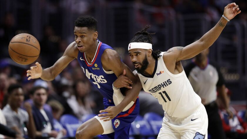 Clippers guard Shai Gilgeous-Alexander battles Grizzlies guard Mike Conley (11) for possession of a loose ball during the second half Friday.