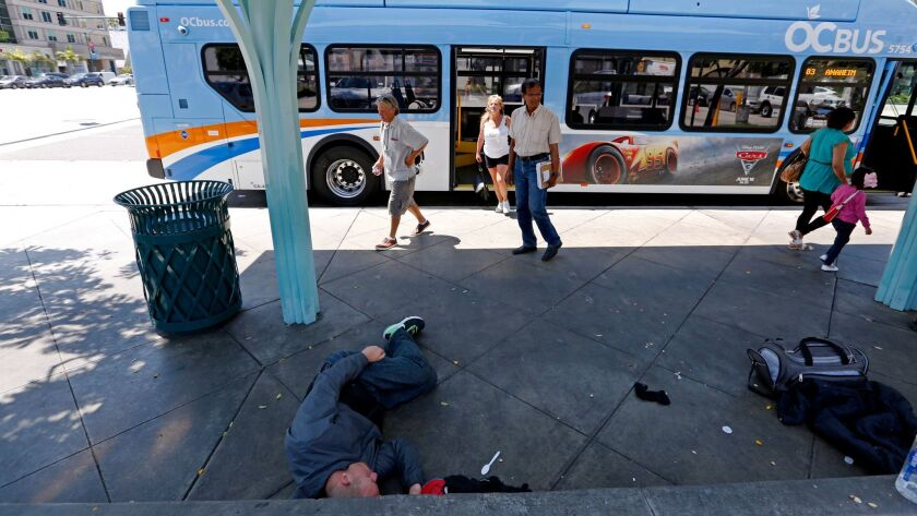A homeless man sleeps under bus shelter while people exit an Orange County Transit Authority bus at