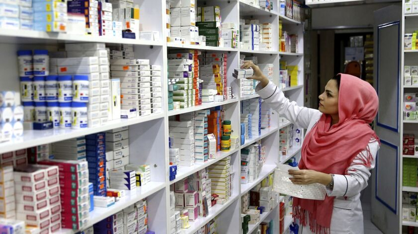 A drugstore employee pics medicine from shelf in downtown Tehran, Iran, Monday, Nov. 5, 2018. Iran g