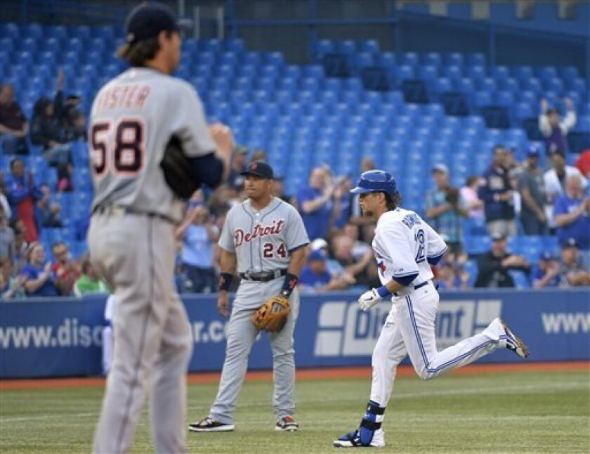 Toronto Blue Jays' Colby Rasmus, right, rounds the bases past Detroit Tigers pitcher Doug Fister, left, and third baseman Miguel Cabrera after hitting a two-run home run during the second inning of a baseball game in Toronto on Tuesday, July 2, 2013. (AP Photo/The Canadian Press, Nathan Denette)