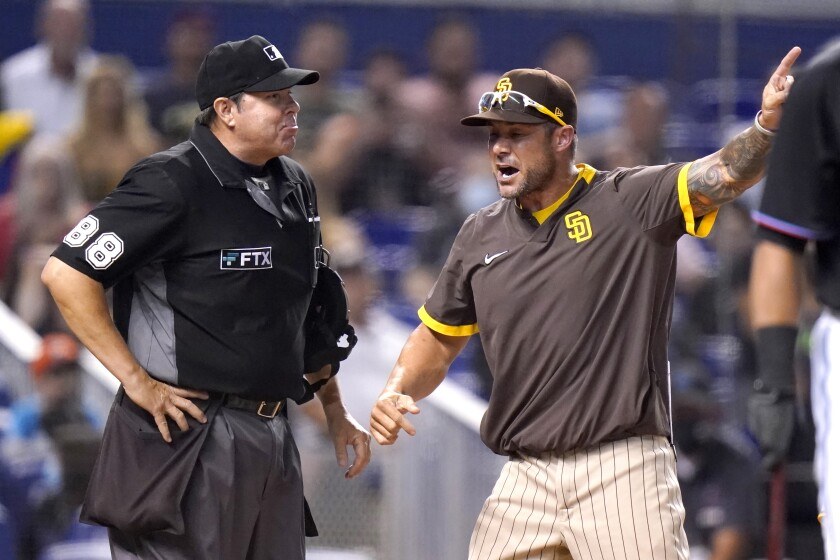 Padres associate manager Skip Schumaker, right, argues with home plate umpire Doug Eddings, left, during Saturday's game.