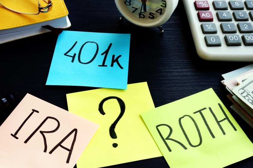 Post-it notes on a desk with the words 401k, Roth, IRA and a question mark.