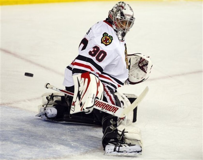 Chicago Blackhawks goalie Ray Emery deflects the puck against the Calgary Flames during overtime of an NHL hockey game in Calgary, Alberta, Saturday, Feb. 2, 2013. The Blackhawks defeated the Flames 3-2 in a shootout. (AP Photo/The Canadian Press, Jeff McIntosh)