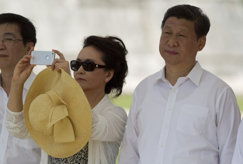 China's President Xi Jinping, right, watches a folk dance presentation as his wife, Peng Liyuan, takes a photograph near the Mayan ruins of Chichen Itza in southern Mexico.