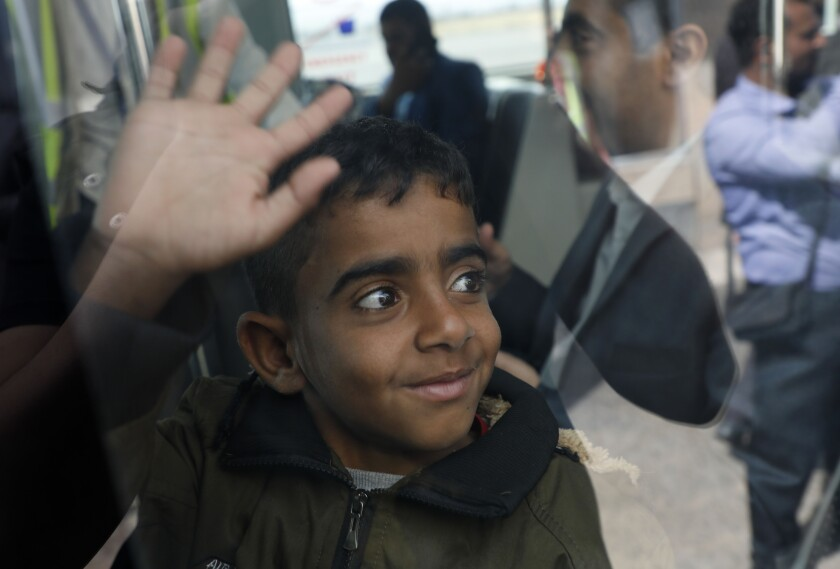 """A Yemeni boy waves from inside a bus before boarding a United Nations plane at Sanaa International airport, Yemen, Monday, Feb. 3, 2020. The United Nations medical relief flight carrying patients from Yemen's rebel-held capital was the first in over three years. The U.N. said eight patients and their families were flown to Egypt and Jordan to receive """"life-saving specialized care not available in Yemen."""" (AP Photo/Hani Mohammed)"""