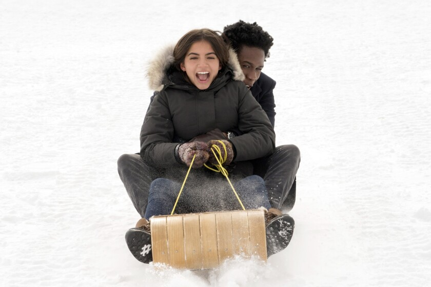 Isabela Merced and Shameik Moore on a toboggan in the movie 'Let It Snow'