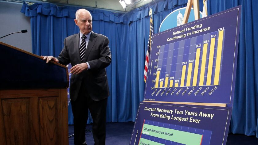 California Gov. Jerry Brown looks over at a pair of charts he used to discuss his revised state budget plan.