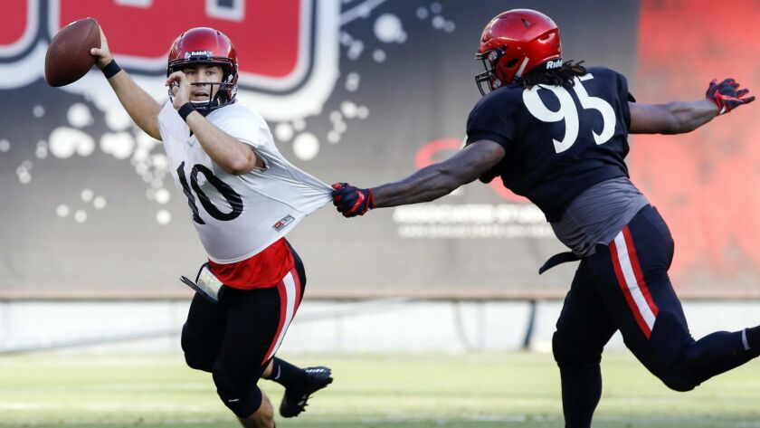 San Diego State defensive lineman Noble Hall grabs quarterback Christian Chapman's jersey for a first half sack during the team's scrimmage Saturday evening at SDCCU Stadium.