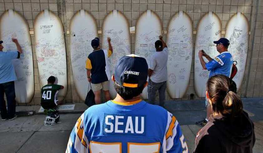 Junior Seau fans leave messages for him on a wall of surfboards at Qualcomm Stadium for a celebration of his life on May 11, 2012.