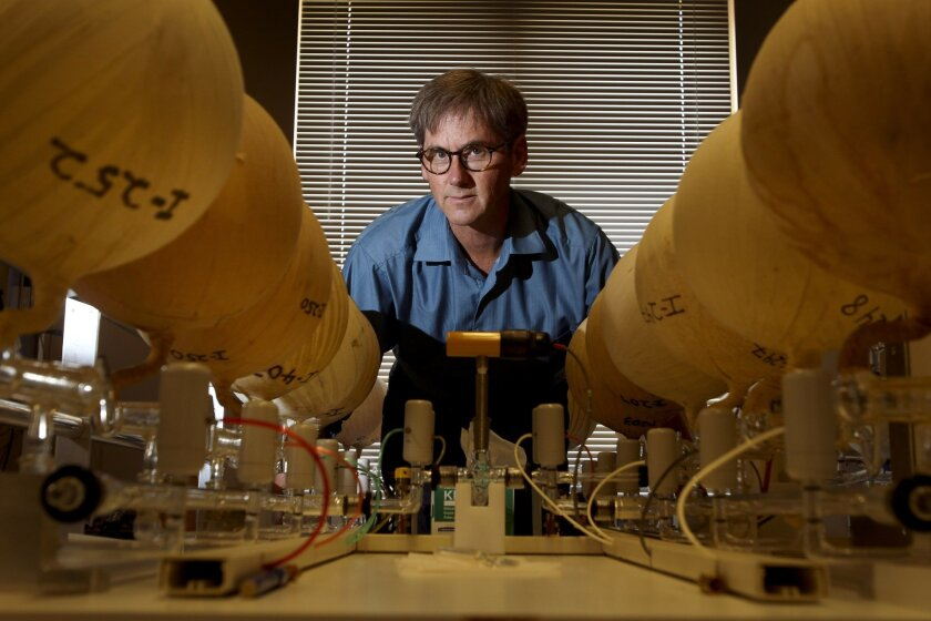 Ralph Keeling stands next to a flask analyzer rack, which contains glass flasks wrapped in tape that are used to measure air samples for carbon dioxide, in his lab at the Scripps Institution of Oceanography in La Jolla. / photo by Hayne Palmour IV * U-T San Diego