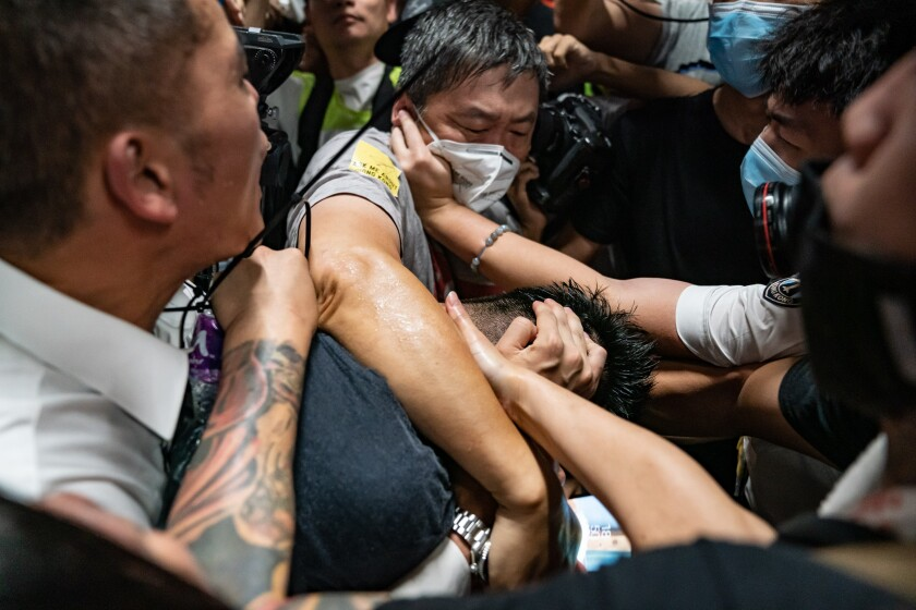 Protesters surround a man they suspect of being an undercover police officer Aug. 13 during a sit-in at Hong Kong's airport.