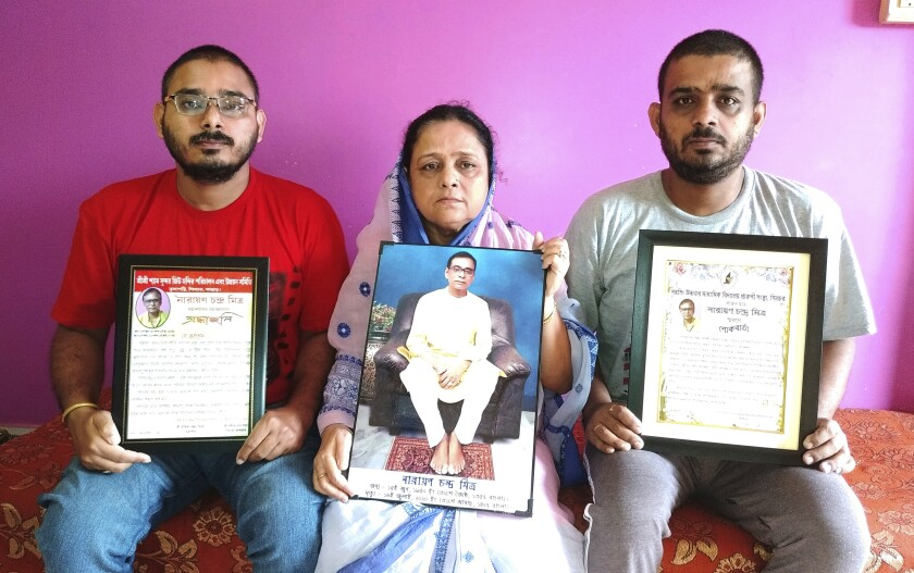 Anindita Mitra, 61, flanked by her sons Satyajit Mitra, right and Abhijit Mitra, pose with portraits of her husband late Narayan Mitra, at her house in Silchar, India, Sunday, Sept. 13, 2020. Narayan Mitra, wasn't listed among those killed by the coronavirus that authorities put out daily because the test results confirming COVID-19 arrived after his death. In India, people who die with other preexisting conditions are often not counted as COVID-19 deaths, while only those who test positive for the virus before dying are included in the official tally in many states. (AP Photo/Joy Roy)