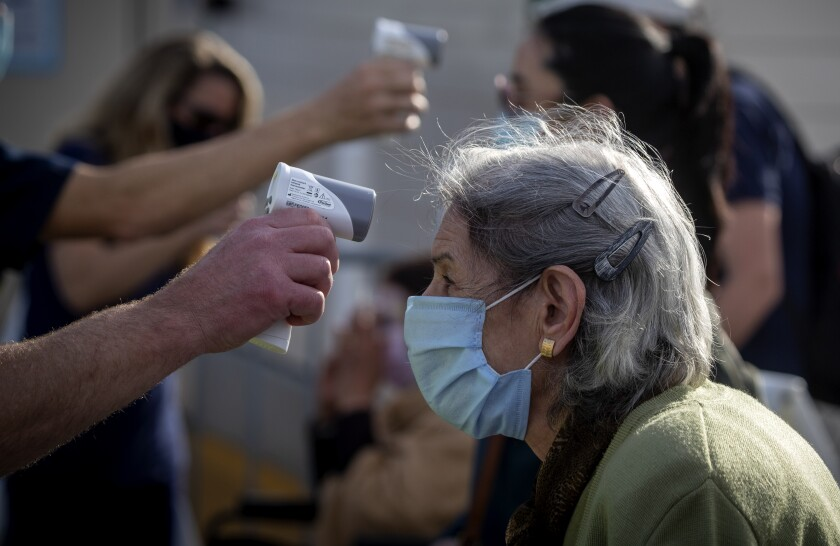 A woman has her temperature taken Wednesday at Disneyland, Orange County's first large-scale COVID-19 vaccination site.