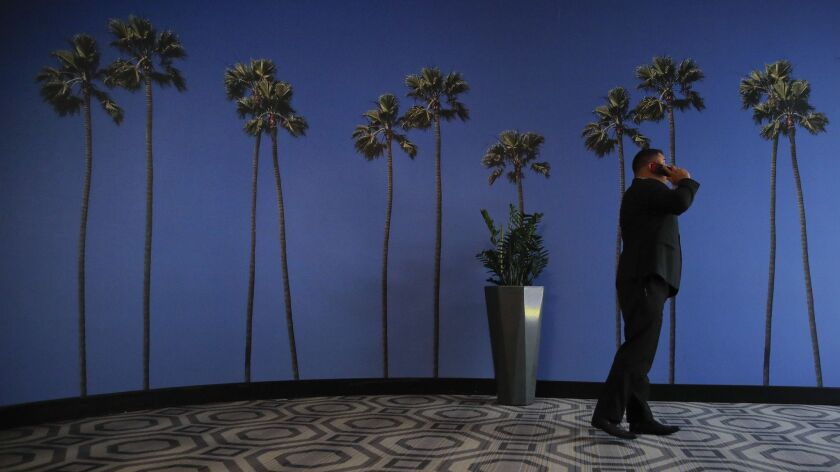 FILE - In this May 4, 2018, file photo a man talks on the phone in a hallway adorned with the palm t