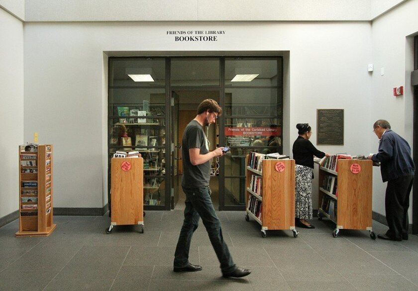 In the entryway of Carlsbad's main library on Dove Lane, a visitor walked past the Friends on the Carlsbad Library Bookstore; other patrons browsed the carts of books. The store sells used books that have been donated.